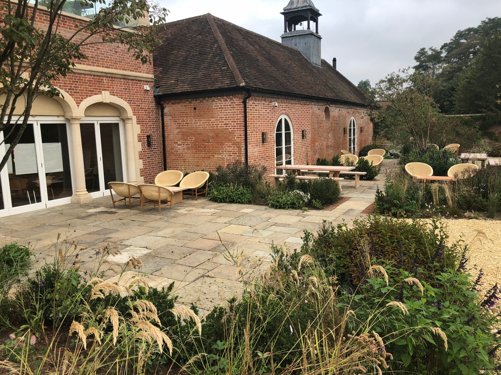 Image of Yorkstone Paving Slabs in a large garden. https://stoneuk.com/products/reclaimed-english-yorkstone-paving/