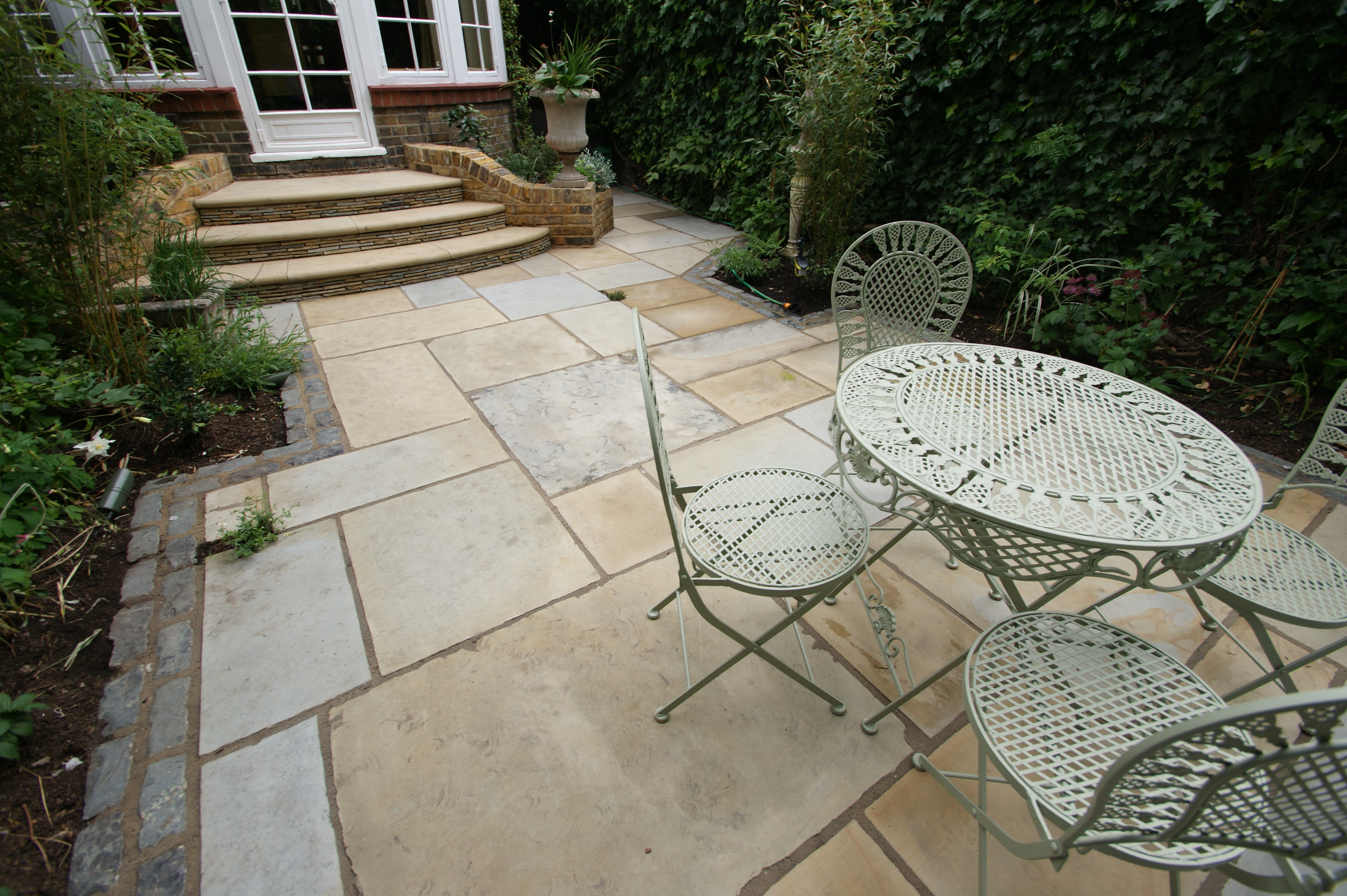 This is an image of reclaimed English yorkstone paving. https://stoneuk.com/products/reclaimed-second-face-english-yorkstone-paving/
